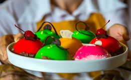 Colorful cake with berries. The confectioner holds a multi-colored cake with berries on a tray. Closeup. Fruity Delicious Biscuit royalty free stock photos