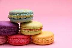 Closeup colorful cake macaron or macaroon on pink background from front view, colorful almond cookies, pastel colors, vintage card royalty free stock photo