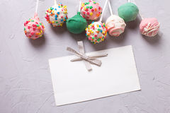 Colorful cake pops and empty tag  on  grey textured  background. Royalty Free Stock Image