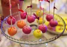 Colorful cake-pops on a glass plate. With satin ribbons on sticks Stock Image