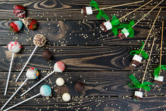 Colorful cakepops and chocolate marshmallows set on wooden background. Colorful cake pops and chocolate marshmallows set on wooden background for text typing Stock Photo