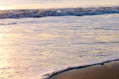 Colorful calm sea waves at sunrise. Sunlit sea waves approaching sand beach Stock Photography