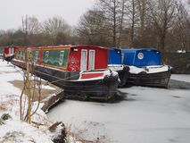 Colorful canal boats moored in the icy water, Kennet and Avon Canal. Colorful canal boats moored in the icy water during winter snow, Kennet and Avon Canal Stock Images