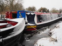 Colorful canal boats moored in icy water, Kennet and Avon Canal. Colorful canal boats moored in icy water during winter snow, Kennet and Avon Canal, Aldermaston Stock Photography