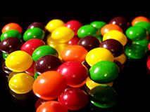 Colorful Candies. This is a close-up photograph of colorful, chewy fruit candies reflected in a mirror.  The green, yellow, purple, red, and orange round candies Stock Photography