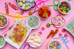 Colorful candies assortment on pink color background, top view stock image