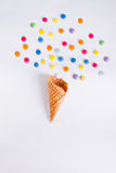 Colorful candies bang from ice cream cone on the white background. Place for lettering. Top view, flat lay. Stock Photo