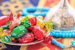 Colorful candies and blue rosary on traditional turkish carpet. Close up Stock Image