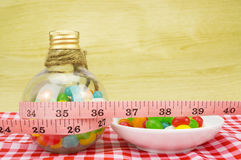 Colorful candies in bottles and tape measure. With shallow depth of field (dof)-diet and healthy teeth concept Stock Image