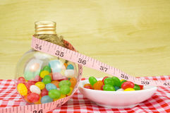 Colorful candies in bottles and tape measure. With shallow depth of field (dof)-diet and healthy teeth concept Stock Photo