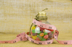Colorful candies in bottles and tape measure. With shallow depth of field (dof)-diet and healthy teeth concept Stock Images