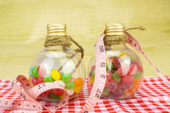 Colorful candies in bottles and tape measure Royalty Free Stock Image