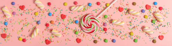 Colorful candies on pink background, top view. Colorful candies on bright pink background, top view Royalty Free Stock Photo