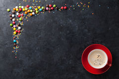 Colorful candies and coffee cup on stone background Stock Image