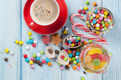 Colorful candies and coffee on wooden table Stock Image