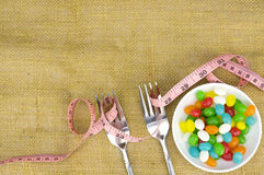 Colorful candies fork and tape measure Stock Photos