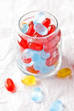 Colorful candies in glass jar. Closeup on white paper background Stock Photo