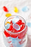 Colorful candies in glass jar. Closeup on white paper background Royalty Free Stock Photos