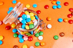 Colorful candies in glass jar on red oranges background stock image