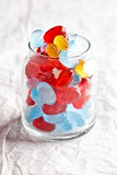 Colorful candies in glass jar. On paper background Stock Photos