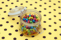 Colorful candies in glass jar. On polka dot napkin Stock Photo