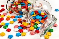 Colorful candies in glass jar scattered on white royalty free stock photos