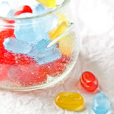 Colorful candies in glass jar. On white paper background Royalty Free Stock Photo