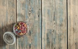 Colorful sugar candy in glass jar on wooden table. Top view. Colorful candies in glass jar on the wooden table with space for your text. Top view Royalty Free Stock Photography