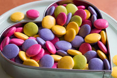Colorful candies. In a heart shaped cookie cutter on a dessert stand Royalty Free Stock Images