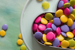 Colorful candies. In a heart shaped cookie cutter on a dessert stand Stock Photography