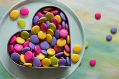 Colorful candies. In a heart shaped cookie cutter on a dessert stand Stock Photos