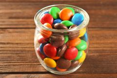 Colorful candies in jar. On wooden background royalty free stock photos