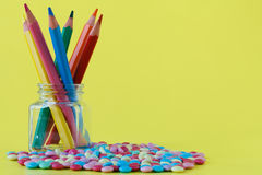 Colorful candies and jar on a yellow background Stock Photo