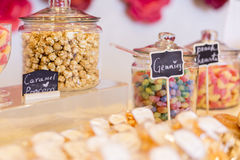 Colorful Candies in jars on a dessert table with donuts, cookies. And popcorn. There are cute chalkboard signs Royalty Free Stock Photo