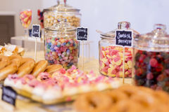 Colorful Candies in jars on a dessert table with donuts, cookies. And popcorn. There are cute chalkboard signs Stock Images