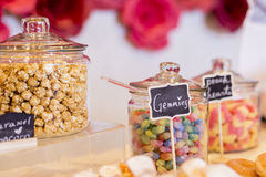 Colorful Candies in jars on a dessert table with donuts, cookies. And popcorn. There are cute chalkboard signs Stock Photo