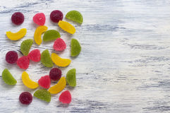 Colorful candies jelly on wooden surface white. Background with marmalade. Stock Photo