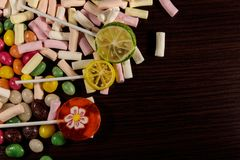 Colorful candies, lollipops and marshmallows on wooden table. Colorful candies, lollipops and marshmallows on the wooden table Stock Images