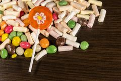 Colorful candies, lollipops and marshmallows on wooden table. Colorful candies, lollipops and marshmallows on the wooden table Royalty Free Stock Photos