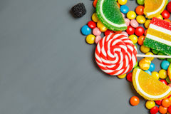 Colorful candies and lollipops over gray background. Top view with copy space Royalty Free Stock Image