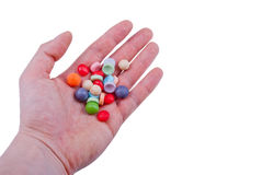 Colorful candies. Male hand holding some colorful candies. Isolated Royalty Free Stock Photos