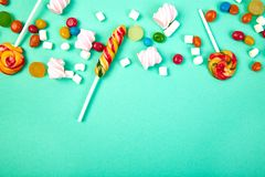 Colorful candies on pastel turquoise background. Flat lay. Top view. Lollipop and Marshmallow on paper background..Copy space royalty free stock photo
