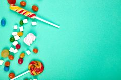 Colorful candies on pastel turquoise background. Flat lay. Top view. Lollipop and Marshmallow on paper background