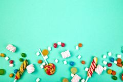 Colorful candies on pastel turquoise background. Flat lay. Top view. Lollipop and Marshmallow on paper background..Copy space stock photo