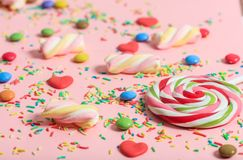 Colorful candies on pink background. View from above, close up Stock Image