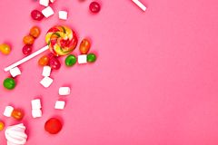 Colorful candies on pink background. Flat lay. Top view. Lollipop and Marshmallow on pink background..Copy space royalty free stock photos