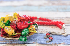 Colorful candies and red rosary on vintage table. Close up Stock Photos