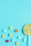 Colorful candies scattered on blue background top view mock up Royalty Free Stock Images