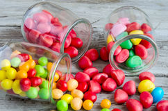 Colorful candies scattered from jars. Close-up of bright scattered on table candies Stock Photography