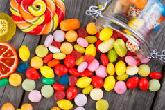 Colorful candies scattered on the wooden table Royalty Free Stock Photos